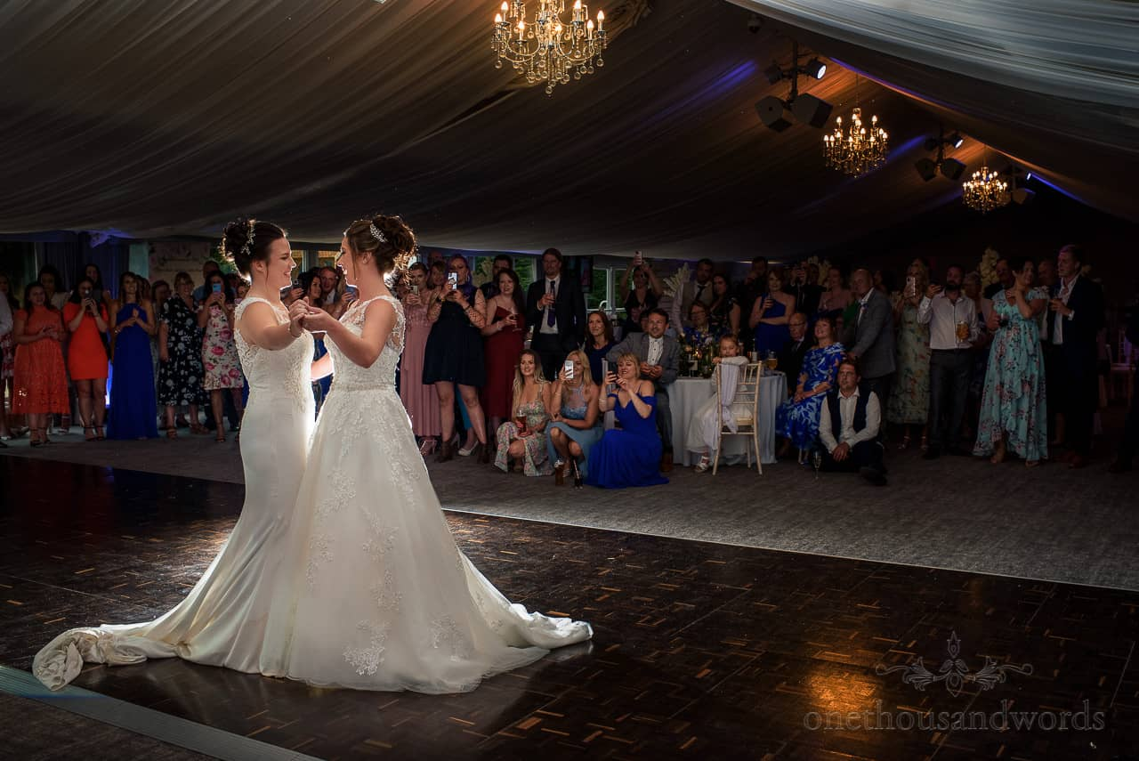 Same sex wedding brides in white dresses first dance at Oakley Hall marquee pavillion guests watching and cheering