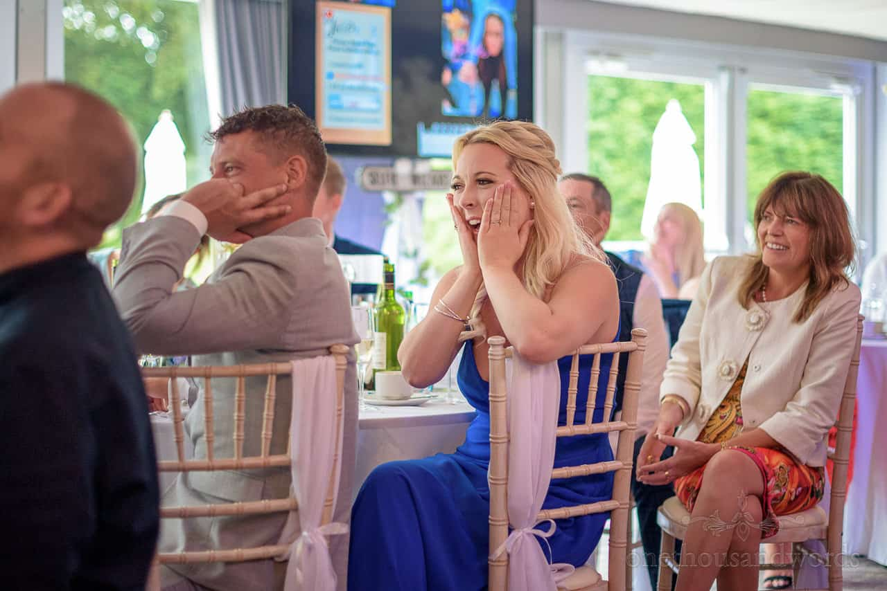 Shocked bridesmaid wearing blue dress laughing at speeches in a wedding marquee