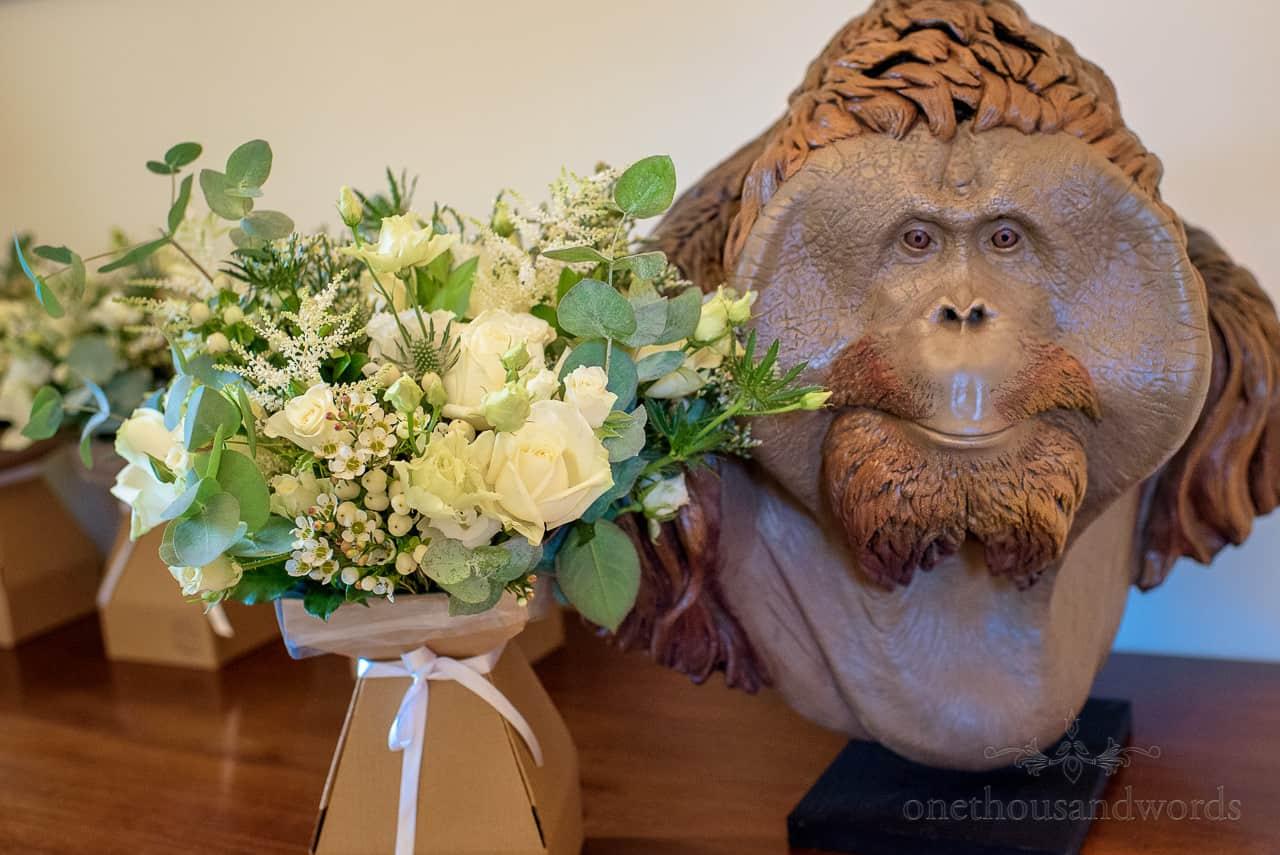 Wedding flower bouquets with orangutan head statue at Monkey World wedding venue