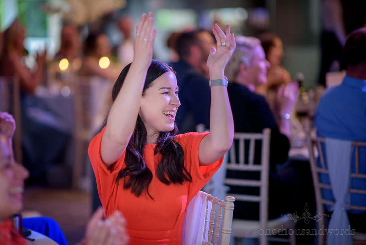 Wedding guest in red dress enthusiastically claps above her head to wedding speeches