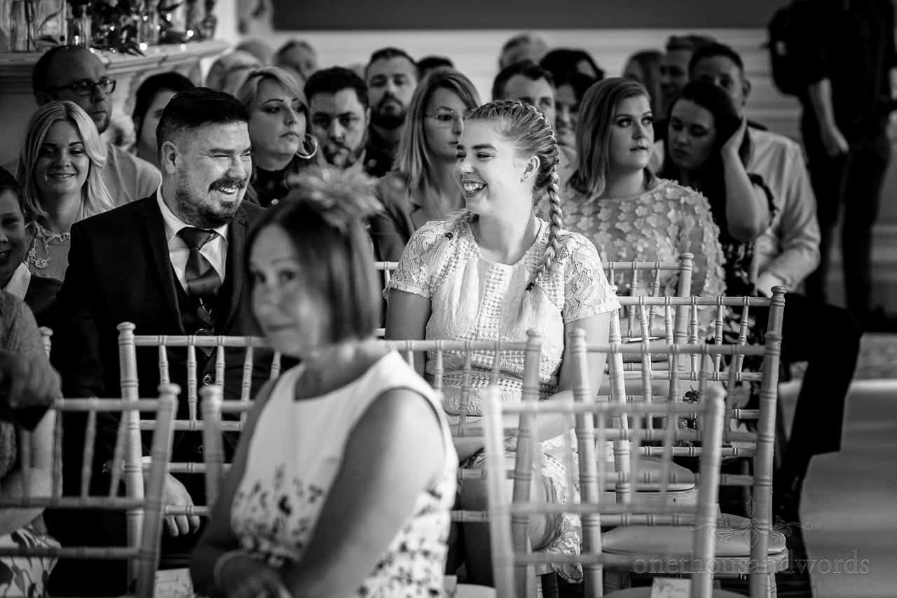 Wedding guests at Oakley Hall wedding ceremony laughing