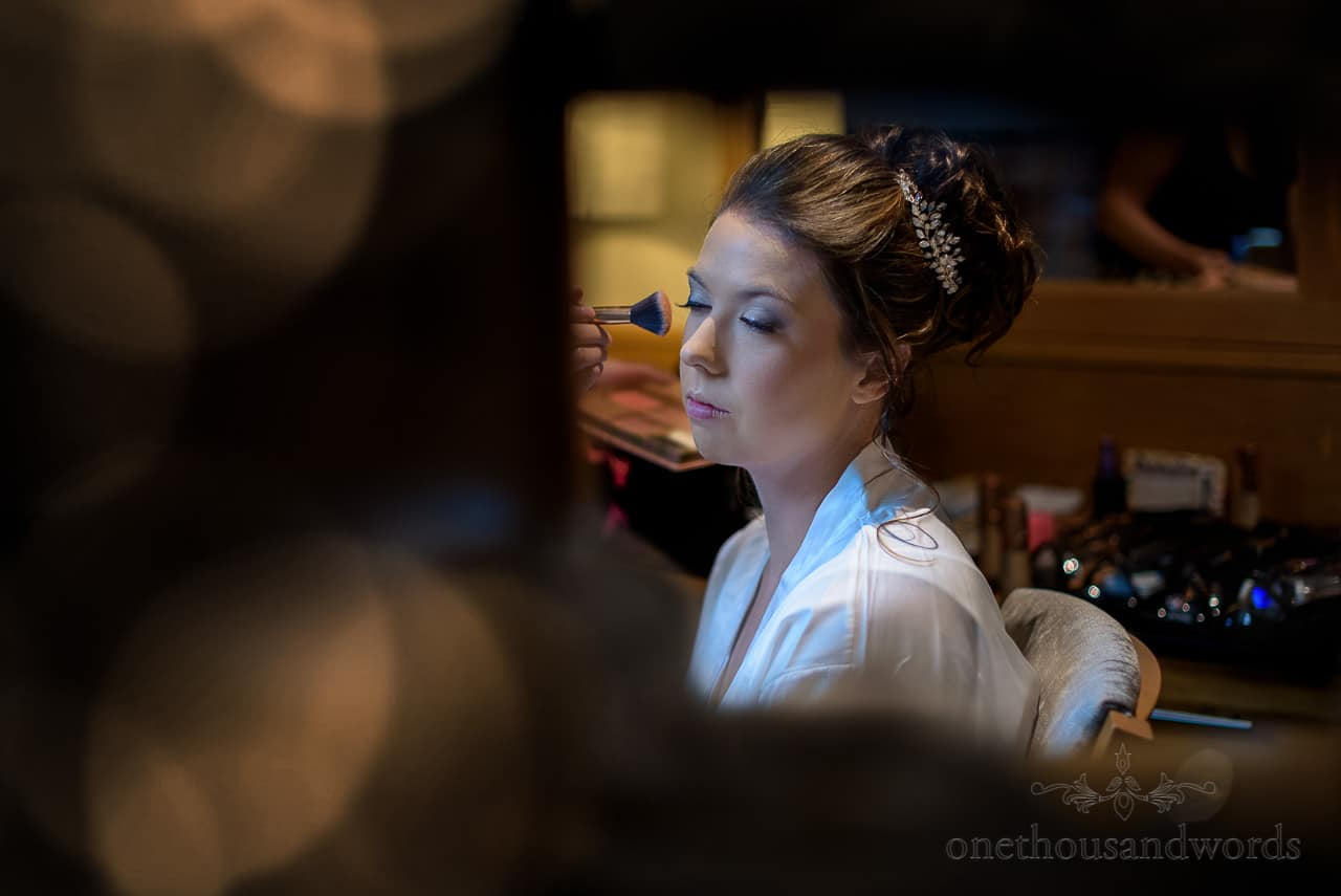 Beautiful bride has makeup applied with brush on wedding morning portrait photo
