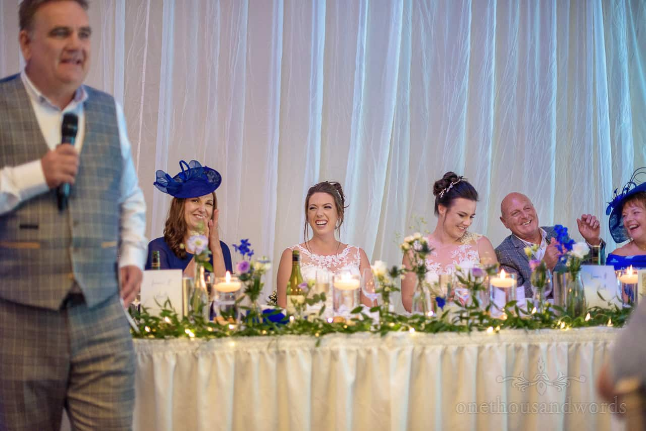 Wedding top table in marquee with two brides laughing and applauding best man's speech
